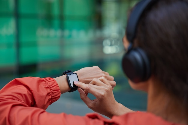 Woman checks results of fitness training on smartwatch listens music via headphones dressed in anorak poses on blurred
