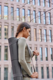 Woman checks time on smartwatch has outdoor fitness going to shake press monitors coned distance carries yoga mat stands sideways on city building