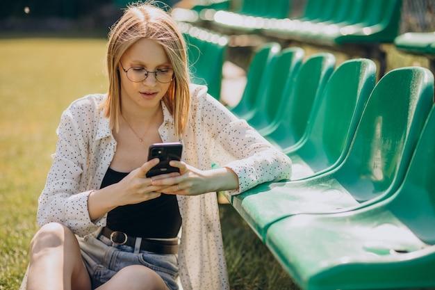 Ragazza pon pon della donna che si siede al campo di calcio