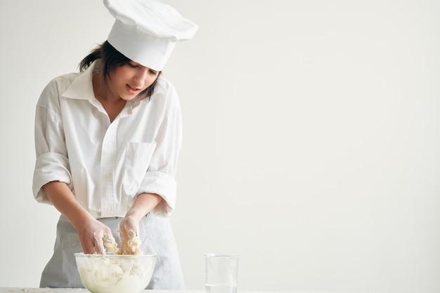 女性シェフのパン屋が生地粉の調理作業を展開します。高品質の写真