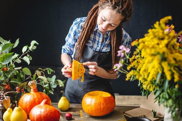 女性シェフがオレンジ色のカボチャを掃除してカボチャのスープを作る