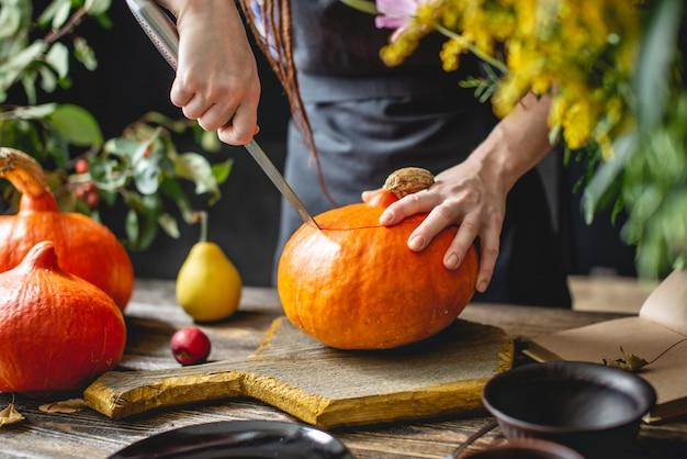 Женщина-повар очищает апельсиновую тыкву, чтобы подготовиться к выпечке