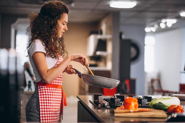 女性シェフが鍋で野菜を調理