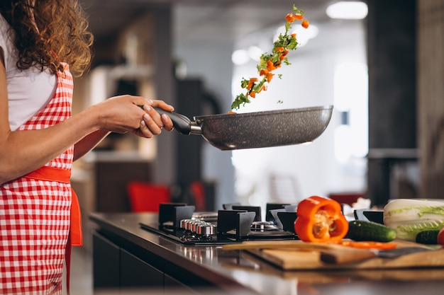 Woman chef cooking vegetables in pan