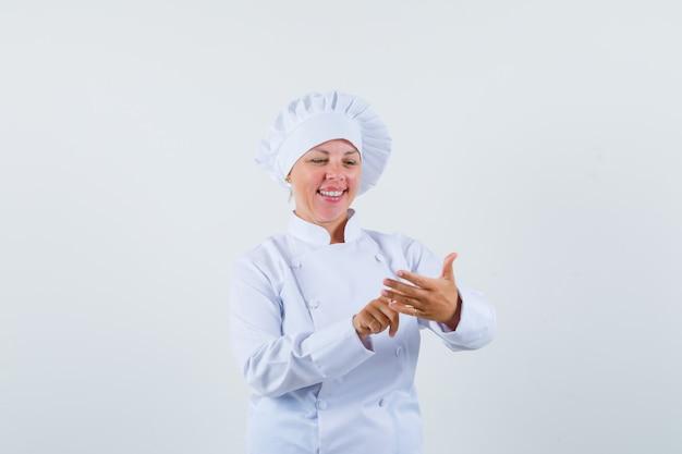 Женщина-повар что-то считает пальцами в белой форме и радостно смотрит