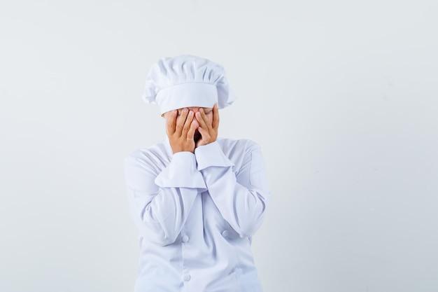 Chef donna che copre il viso con le mani in uniforme bianca e in cerca di vergogna