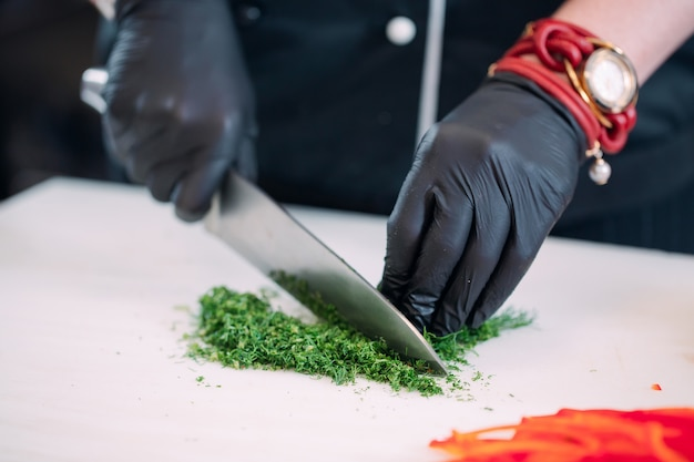 A woman chef cuts vegetables in the kitchen in a restaurant