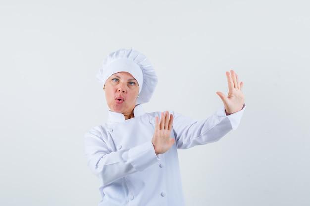Chef donna difendendosi in uniforme bianca e guardando ansioso