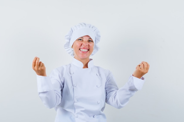 Woman chef doing money gesture in white uniform and looking happy.