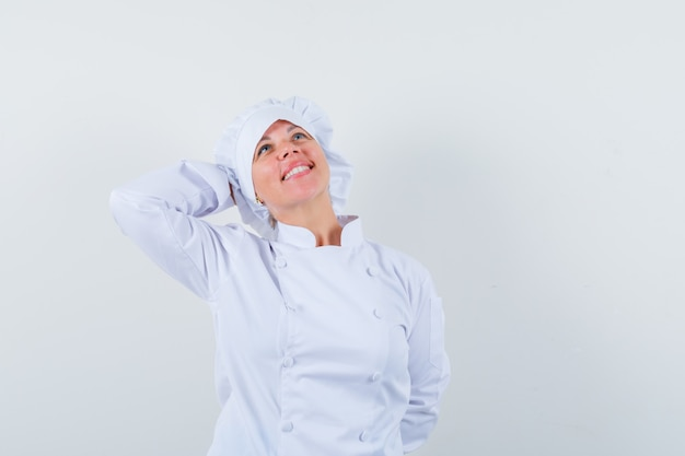 白い制服を着て頭の後ろで手をつないでリラックスして見える女性シェフ。