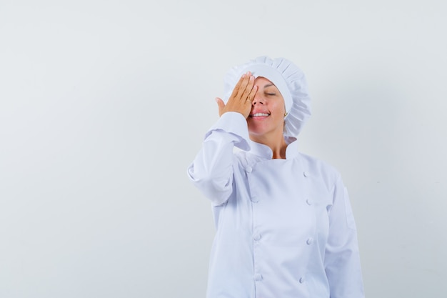 Woman chef holding hand on eye in white uniform and looking peaceful