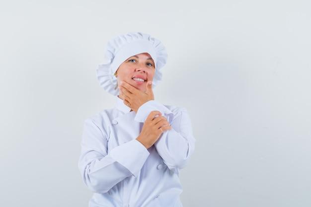 白い制服を着たあごに手をつないで、賢明に見える女性シェフ。