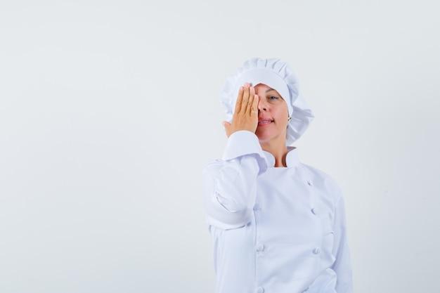 白い制服を着て、自信を持って目をつないでいる女性シェフ