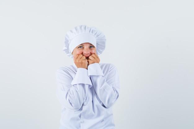 Chef donna che tiene le mani sulle guance in uniforme bianca e dall'aspetto carino