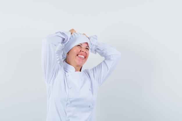 Chef donna tenendo le mani sulla testa in uniforme bianca e guardando beato.