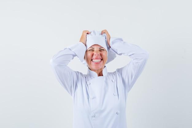 Chef donna tenendo le mani sulla testa in uniforme bianca e guardando felice.