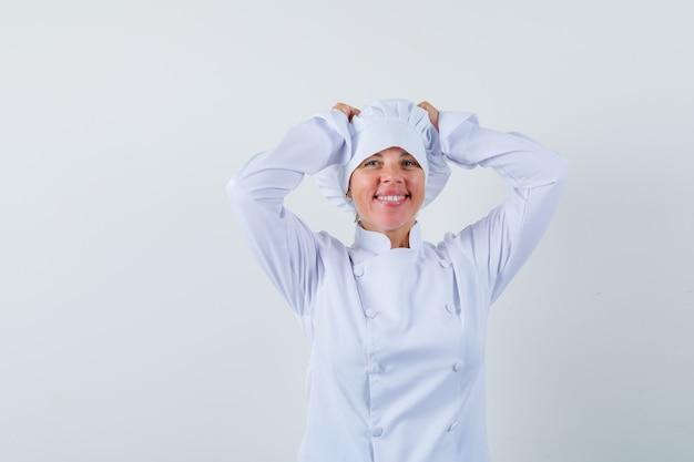 Chef donna tenendo le mani sulla testa in uniforme bianca e guardando gioioso