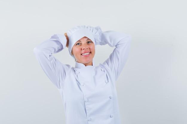 Chef donna tenendo le mani sulla testa in uniforme bianca e cercando pacifica.