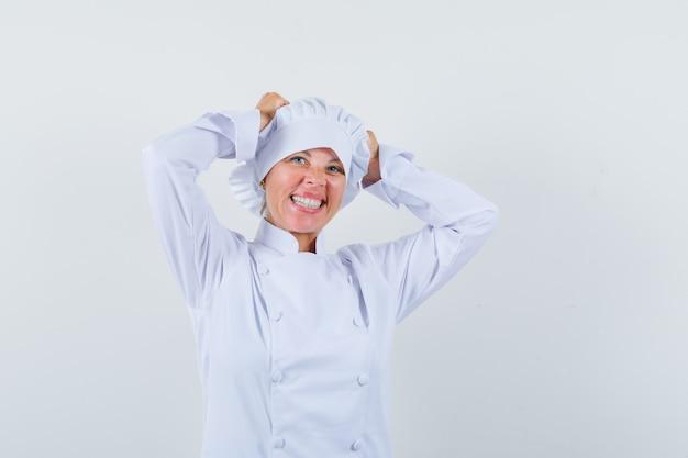 白い制服を着て頭に手をつないで幸せそうに見える女性シェフ。