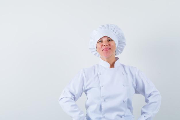 白い制服を着て腰に手をつないで自信を持って見える女性シェフ