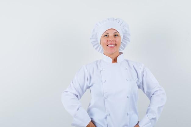 Chef donna tenendo le mani sulla vita in uniforme bianca e guardando fiducioso