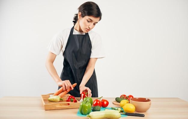Женщина-шеф-повар в черном фартуке нарезка овощей приготовление пищи здоровой пищи в доме
