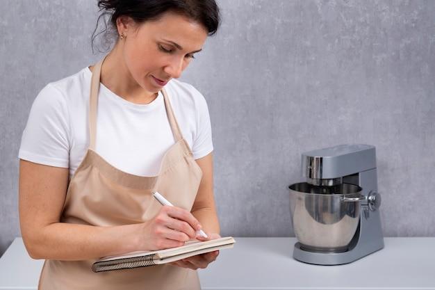 キッチンローブの女性シェフが料理本にレシピを書いています。ポートレートクック