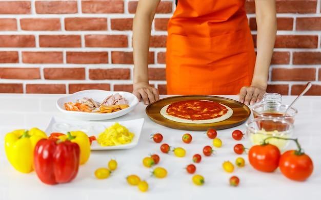 Женщина-повар в оранжевом фартуке готовится приготовить вкусную здоровую пиццу на деревянной тарелке с множеством свежих красных и желтых помидоров, мяса, органических ингредиентов и приправ на белом столе у кирпичной стены
