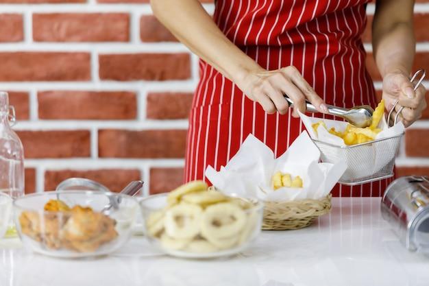 Женщина-повар в красном полосатом фартуке сжимает вкусный жареный картофель, чтобы поделиться им от металлического сита до плетеной корзины на кухонном столе у кирпичной стены на домашней кухне, чтобы разложить еду на блюдах перед подачей на стол