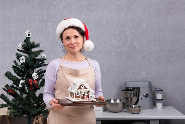 サンタ帽子をかぶった女性シェフがジンジャーブレッドハウスを手にしています。キッチンのクリスマスデコレーション。