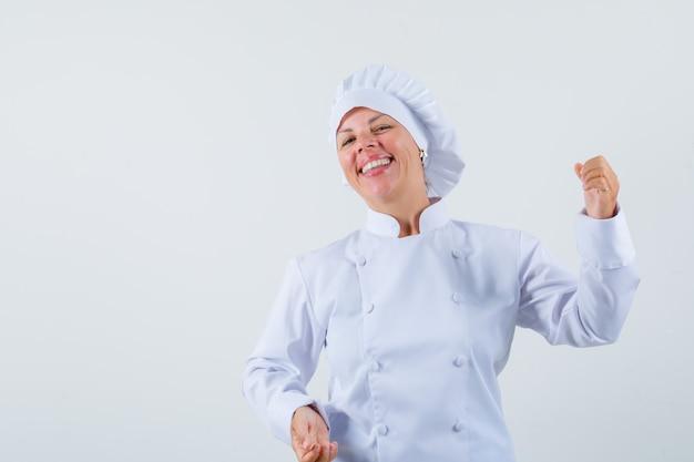 Женщина-повар в белой форме позирует, как держит что-то и выглядит весело