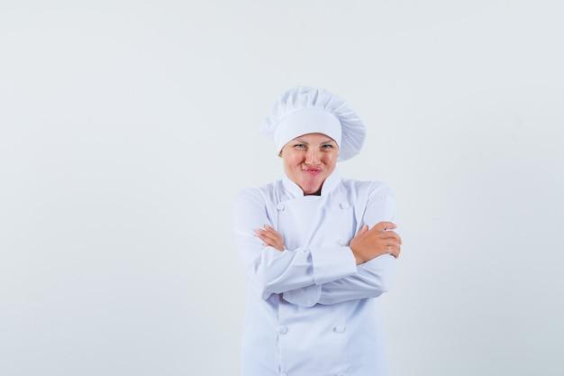 팔을 교차 포즈와 유쾌한 찾고 흰색 유니폼에 여자 요리사