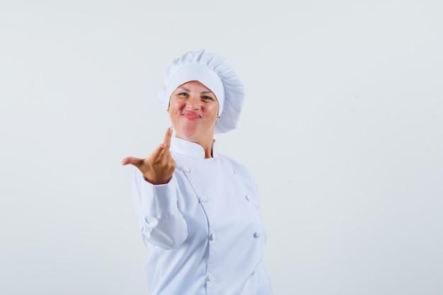 白い制服を着た女性シェフが疑問を持って手を上げて元気に見える