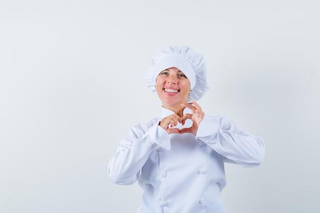 흰색 제복을 입은 여자 요리사가 심장 제스처를 보이고 명랑 한 찾고
