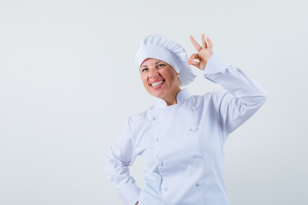 확인 제스처를 표시하고 텍스트에 대한 만족 된 공간을 찾고 흰색 제복을 입은 여자 요리사