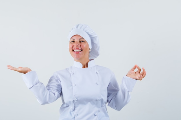 Женщина-повар в белой униформе показывает жест