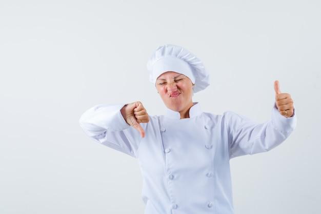 Женщина-повар в белой форме показывает большой палец вверх и вниз и выглядит нерешительно