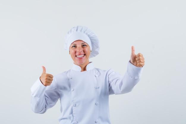 Женщина-повар в белой униформе показывает большой палец вверх и выглядит оптимистично