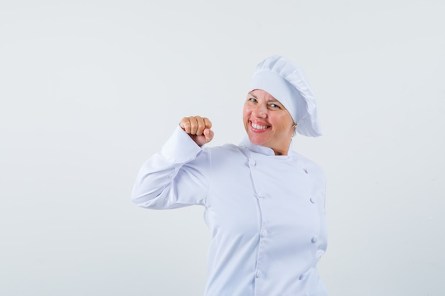 Женщина-повар в белой форме показывает жест победителя и выглядит счастливой