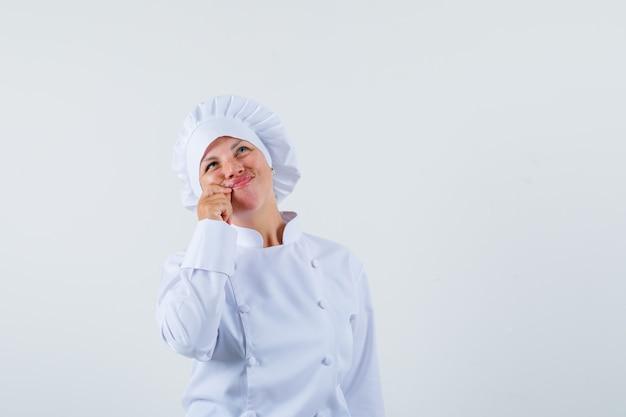 Женщина-повар в белой униформе показывает жест на молнии и выглядит спокойно