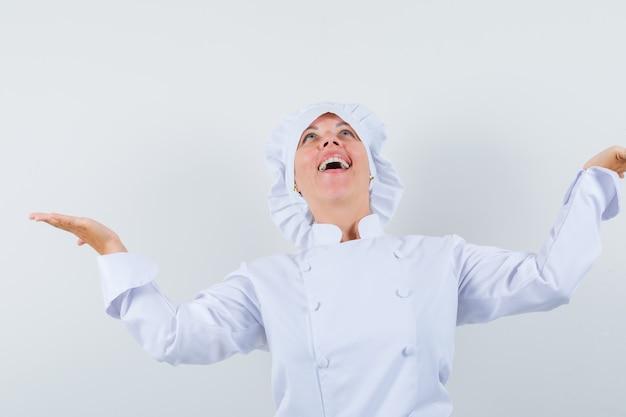 見上げて幸せそうに見える間脇に手のひらを広げている白い制服を着た女性シェフ