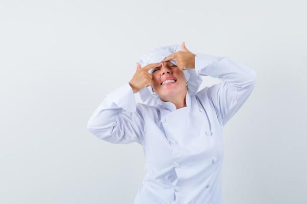 額に彼女のにきびを絞る白い制服を着た女性シェフ