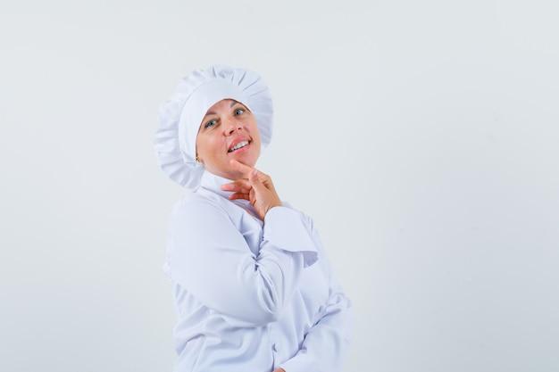 손가락으로 그녀의 턱을 만지고 매력적인 찾고 흰색 제복을 입은 여자 요리사