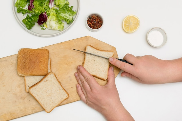Женщина-повар готовит, режет хлеб для жарки гренок и добавляет в салатные листья.