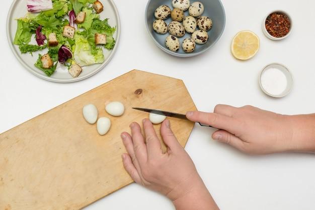 Женщина-повар готовит, режет перепелиные яйца, добавляет их в миску.