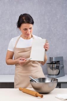 女性シェフが料理教室を開催しているキッチンで料理本を持っています。垂直フレーム。