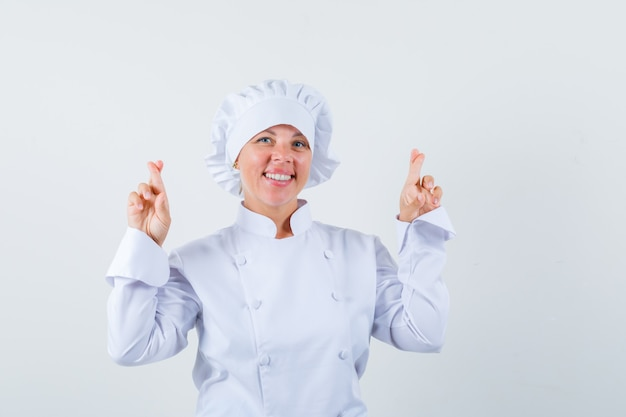 Chef donna tenendo le dita incrociate in uniforme bianca e guardando allegra