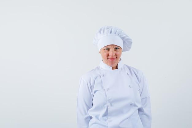 Chef donna guardando davanti in uniforme bianca e guardando scontento.