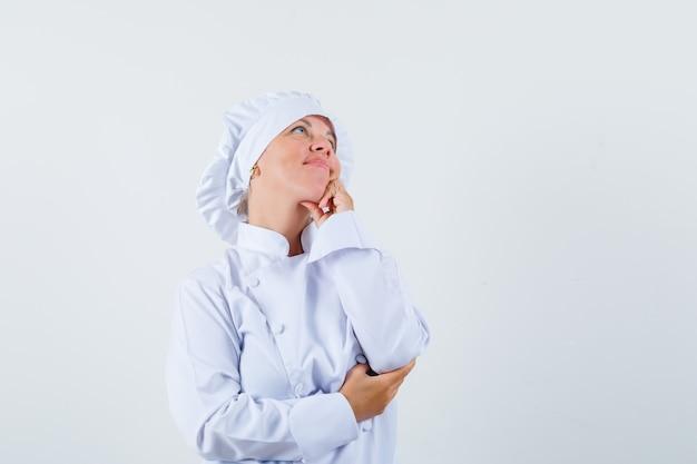 Chef donna che osserva in su in uniforme bianca e che sembra sognante
