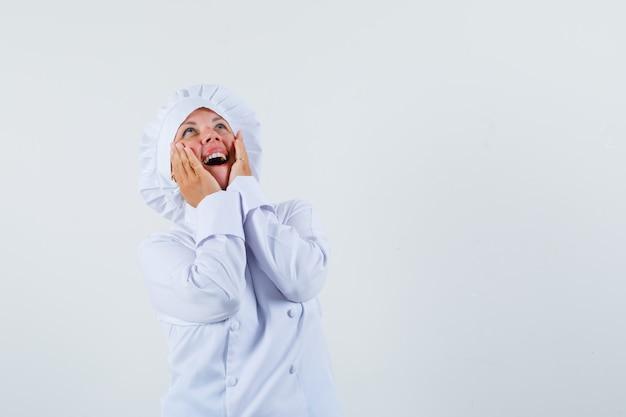 Chef donna alzando lo sguardo con le mani sul viso in uniforme bianca e cercando lo spazio contento per il testo